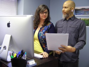 Graphics team standing in front of a Mac Computer